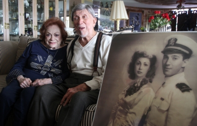 Selma and Ben Z. Grenald pose together in their Miami Shores apartment next to their wedding photo taken in June, 1943, on Tuesday, April 9, 2013. Grenald was serving in the Navy in May of 1943 when he helped with the capturing of eight German prisoners of war that had escaped from the Queen Mary ship, docked next to his post.