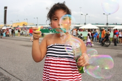 Lisa Alicea, age 5, blows bubbles at her family, not pictured, as they enjoy the Fourth of July festivities held at the Homestead-Miami Speedway on Sunday, July 4, 2010.